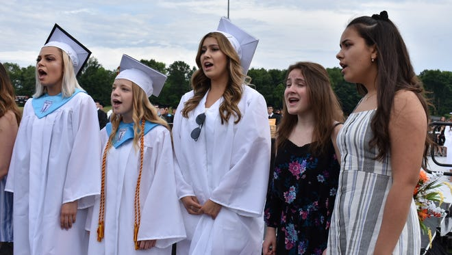 Students sing the National Anthem before the graduation ceremony at Marlboro High School starts.