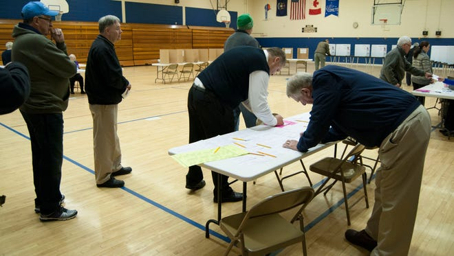 Voters stand in line at 7 a.m. Tuesday morning at Precinct 3 at Crull Elementary School in Port Huron waiting to vote right as the polls open.