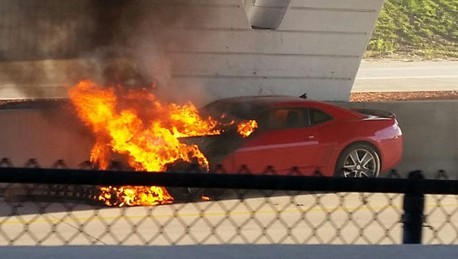 A witness took this photo of the burning Camaro allegedly crashed on Interstate Highway 235 Saturday afternoon by Steve Luebke.