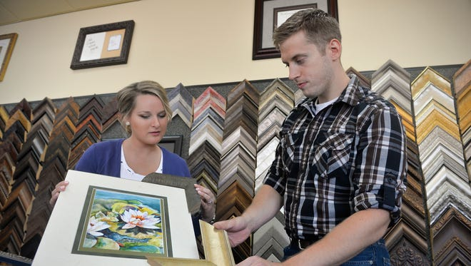Goldeneye Framing & Gallery co-owners Beth and Mike Griffin look over possible frames for a matted piece of art for the gallery Friday, July 1, 2016, at the Waite Park store. The couple formally took over in January for Beth's dad, who previously ran the store.