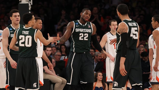 Michigan State guard/forward Branden Dawson (22) celebrates with guard Travis Trice (20) and guard Denzel Valentine (45) during the first half against the Virginia Cavaliers at Madison Square Garden.