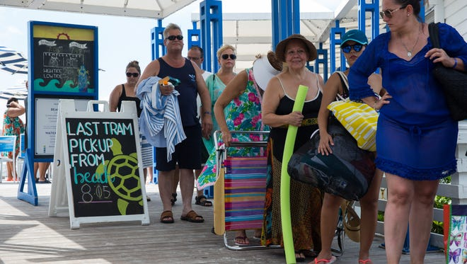 Beachgoers wait in line for the tram service at the Clam Pass Park beach access point in Naples on Saturday, Sept. 10, 2016. The boardwalk at Clam Pass Park is about three quarters of a mile long and can be walked or visitors can catch a ride on a free tram that runs continuously throughout the day until dusk.