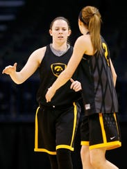 Iowa's Samantha Logic, left, walks over to slap hands