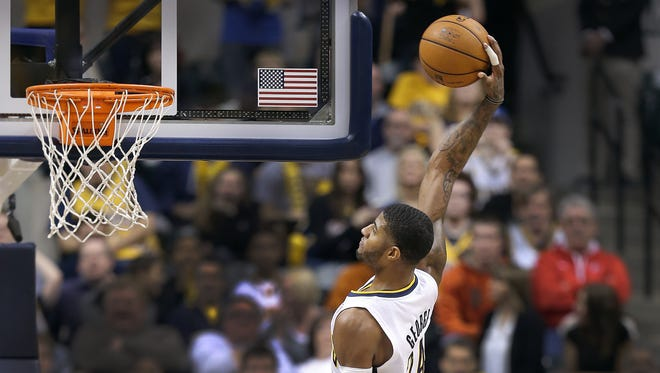 Indiana Pacers Paul George,right, goes high to dunk on Cleveland Cavaliers Anderson Varejao,left, in the fourth quarter of their game. Indiana Pacers host the Cleveland Cavaliers Wednesday, December 31m 2013, afternoon at Bankers Life Fieldhouse.
