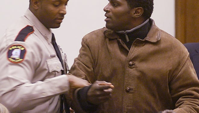 Anthony Hervey (right) of Oxford is escorted from the room by Capitol Police officer Kermit Tate after Hervey began shouting during a meeting of the Mississippi Flag Commission in 2000. Hervey died in a car accident Sunday.
