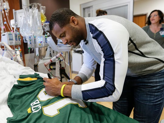Randall Cobb signs a jersey for a patient at Froedtert