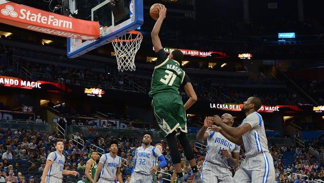 Bucks center John Henson soars to the basket for a dunk Sunday night in Orlando.