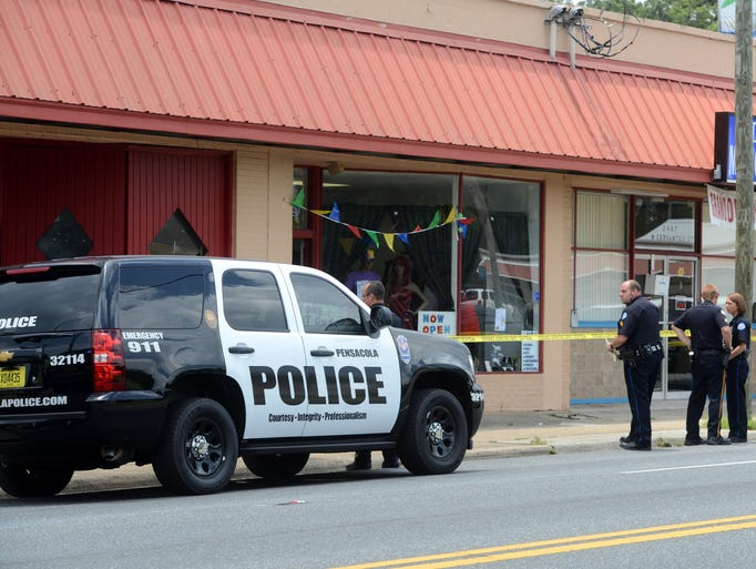 Pensacola Police Officers work the scene of a fatal shooting Wednesday at 2405 West Cervantes Street. A female store employee was shot twice and killed by her boyfriend after an argument at the store. The suspect fled the scene but later turned himself in at the Escambia County Jail where he is being questioned.