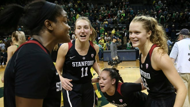 Stanford's Nadia Fingall, left, Alanna Smith, and Marta Sniezek celebrate with Brittany McPhee, right, after she led the team in scoring to defeat Oregon in an NCAA college basketball game in Eugene, Ore., Sunday, Feb 4, 2018.