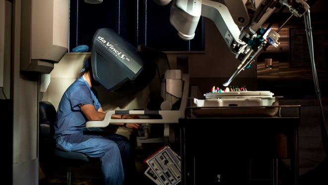 Steve Schlitt demonstrates how the surgeon console is used for the da Vinci surgical robot at McLaren Port Huron. Schlitt, the da Vinci specialist at McLaren Port Huron, has overseen nearly 1000 surgeries be performed with the machine .