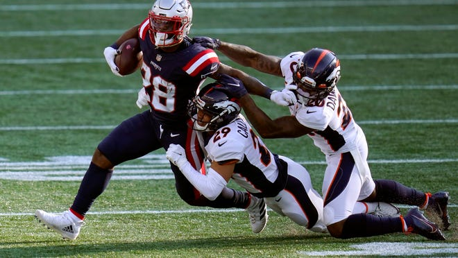 Denver Broncos cornerbacks Bryce Callahan (29) and Duke Dawson Jr. (20) tackle New England Patriots running back James White (28) in the second half of an NFL football game, Sunday, Oct. 18, 2020, in Foxborough, Mass.