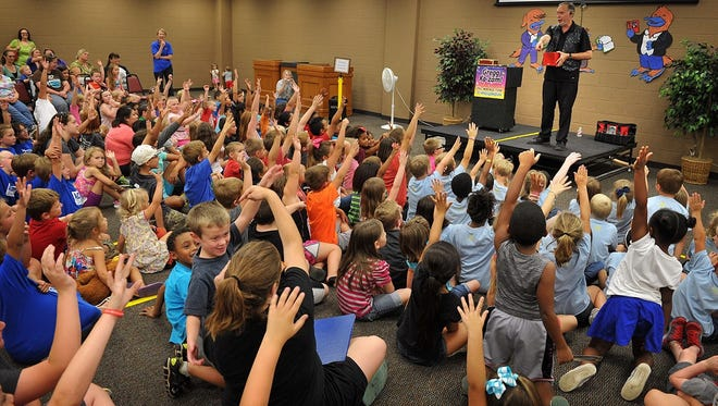 Magician Gregg Ka-Zam calls for a volunteer from the audience during his magic show in 2015 at the Wichita Falls Public Library. The library closed Tuesday and will remain closed Wednesday because of flooding caused by a malfunctioning sprinkler head. The children's department was the area affected, said library administrator Lesley Daly.