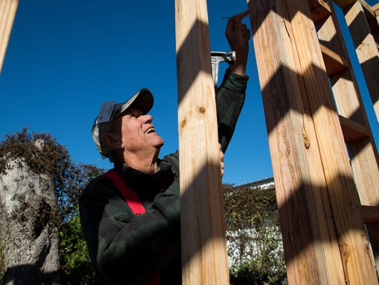 Al Schmidt of Illinois hammers a nail as he helps build