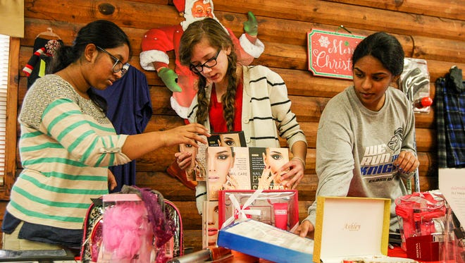 From left, Neha Konatreddy, 16, of West Windsor, Morgan Zielinski, 15, of East Brunswick, and Thanmayee Maddipati, 15, of Plainsboro work on a display together as Middlesex County 4H teens and preteens set up their gifts in the 4H cabin at Middlesex County Fairgrounds in East Brunswick on Saturday December 12, 2015 for their annual Project Gift event on Sunday.