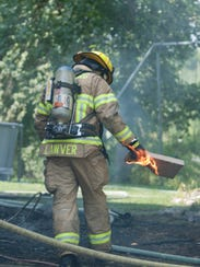 A firefighter removes a burning item from the house