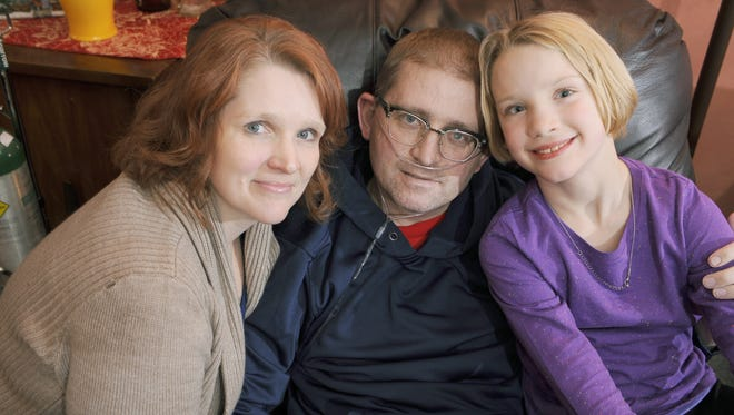 Sara and Jason Gooley spend time with daughter Madeline, 9, at home Thursday.