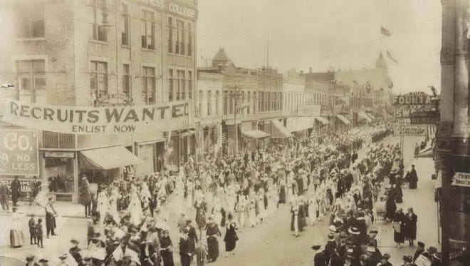 "A group of Red Cross nurses parades past Merritt Avenue during an Oshkosh Preparedness Parade down Main Street during World War I. The Oshkosh Business College, left, displays a large banner that states ""Recruits Wanted. Enlist Now."""