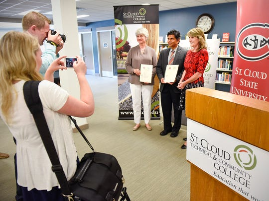 St. Cloud Technical & Community College PresidentÊJoyce Helens, St. Cloud State University Interim President Ashish Vaidya and SCTCC Interim President Lori Kloos, show the signed partnership agreement between the two schools Wednesday, July 12, at SCTCC.