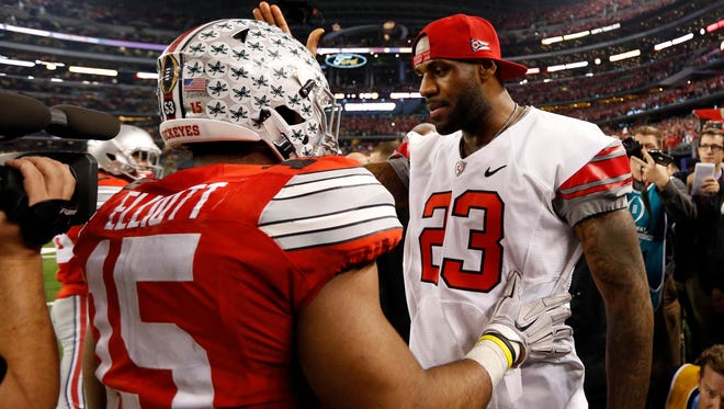 Ohio State Buckeyes running back Ezekiel Elliott (15) greets Cleveland Cavaliers player LeBron James in the fourth quarter against the Oregon Ducks in the 2015 CFP National Championship Game at AT&T Stadium.