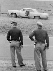 1st April 1965:  Two Alabama state troopers standing over the road from the wreck of the car belonging to the murdered Detroit housewife, Viola Liuzzo, who was killed by a group of Ku Klux Klansmen (KKK) after having taken part in a civil rights march from Selma to Montgomery.  (Photo by William Lovelace/Express/Getty Images)