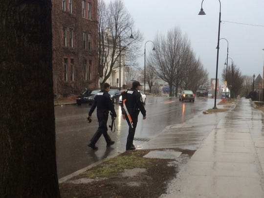 Burlington police officers walk on College Street, where the department responded to a call of a suicidal person on Monday.