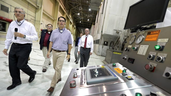 Managing Director Doug Osterberg, left, leads Gov. Scott Walker on a plant tour before the announcement of $1.8 million in state tax credits from the Wisconsin Economic Development Corporation to support Midwest Paper Group's effort to modernize the former Appleton Coated paper mill on Monday in Combined Locks. Midwest Paper Group has pledged to create 321 jobs and invest $30 million.