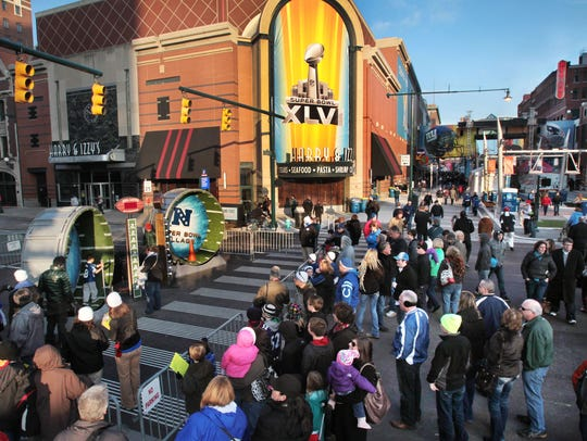 Crowds gather at the intersection of South Illinois, left, and Georgia Street, right, to watch participants run the 100-yard Hampster Wheel Dash, left, in the Super Bowl Village, where Indianapolis' big Super Bowl party got underway Friday afternoon, Jan. 27, 2012.