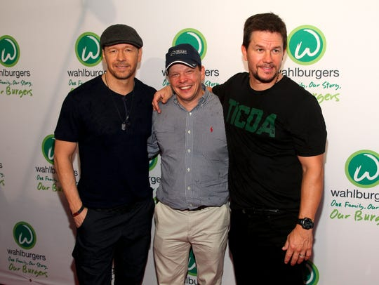 Donnie Wahlberg (from left), Paul Wahlberg and Mark Wahlberg attend the Wahlburgers Coney Island preview party in New York in 2015. A Wahlburgers restaurant is coming to Brookfield this summer.