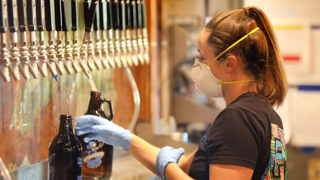 Rachel Ahrens, an assistant manager at First Magnitude Brewing Company, fills growlers with beer while wearing a protective mask and gloves May 5 at the brewery and tap room in Gainesville. Since the lockdown for the COVID-19 pandemic, First Magnitude has been working to keep their business going. They are offering a drive thru beer pick-up where customers can get growlers or cans and bottles of their beer without getting out of their cars and while employees keep proper social distance while wearing protective mask and gloves.
