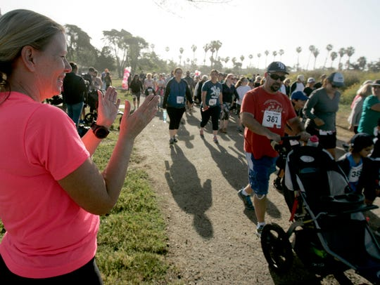 Suellen Lindquist (left), race director for a past Mom's Day Run, cheers on runners in the race at San Buenaventura State Beach. The race benefits The VHL (Von Hippel-Lindau syndrome) Alliance.
