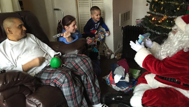 David McKay of Canton Township in a Santa Claus costume gives a gift to AJ Ortega, 5, and his parents in the Ortegas' home in southwest Detroit. Santa is a volunteer with Jimmy's Kids on Sunday, Dec. 25, 2016.