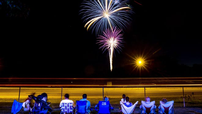 Fireworks explode over the sky as the blur of car lights along I-55 from a long exposure silhouette the spectators taking in the fireworks from the Illinois State Police Academy during Rock the Dock on Lake Springfield , Friday, June 24, 2016, in Springfield, Ill.