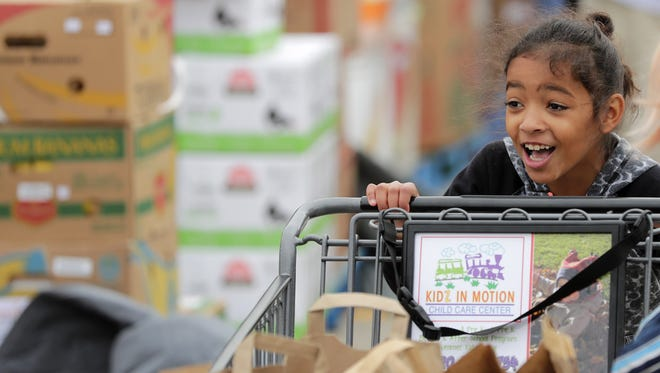 An 8-year-old girl pushes her family's cart at a 2016 mobile food pantry event in Green Bay that was part of USA TODAY NETWORK-Wisconsin's annual Stock the Shelves campaign.