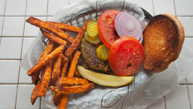 The Shady Lane veggie burger served on a golden brioche and garnished with lettuce, tomato, onion and dill pickle chips, a dill pickle spear and sweet potato fries ($7.50).