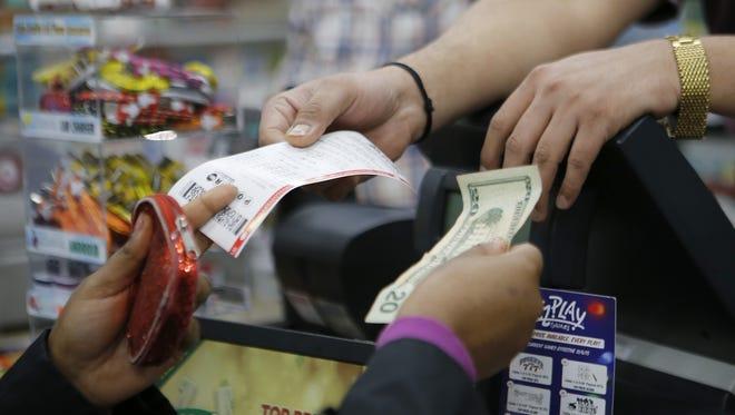 Sudhakar Gundaji sells Powerball lottery tickets at Garfield Mini-Mart in downtown Cincinnati on Wednesday, Jan. 6, 2016. Wednesday's Powerball jackpot is an estimated $700 million.