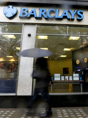 Pedestrians pass a branch of Barclays Bank in the rain in London.