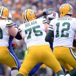 Green Bay Packers quarterback Aaron Rodgers (12) tries to find a receiver behind the blocks of T.J. Lang (70) and Bryan Bulaga (75) against the Buffalo Bills at Ralph Wilson Stadium in Orchard Park, N.Y., December 14, 2014.