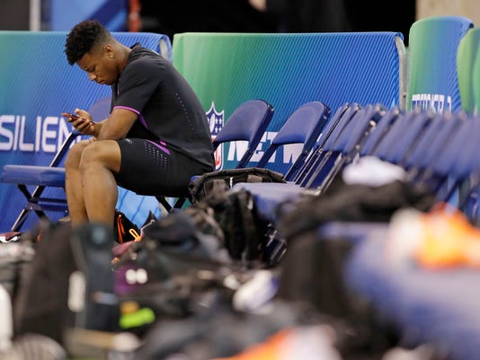 Penn State running back Saquon Barkley looks at his phone during the NFL football scouting combine, Friday, March 2, 2018, in Indianapolis. (AP Photo/Darron Cummings)
