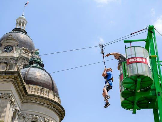 Eli Barfield, 8, of Newburgh, left, receives encouragement from Get Your Game On, Inc. employee Toby Arwine, right, while sliding down the Mobile Zip Line set up beside the Old Vanderburgh County Courthouse during the Lunch on the Lawn Bicentennial Birthday Bash in Downtown Evansville, Ind., Friday, July 6, 2018.
