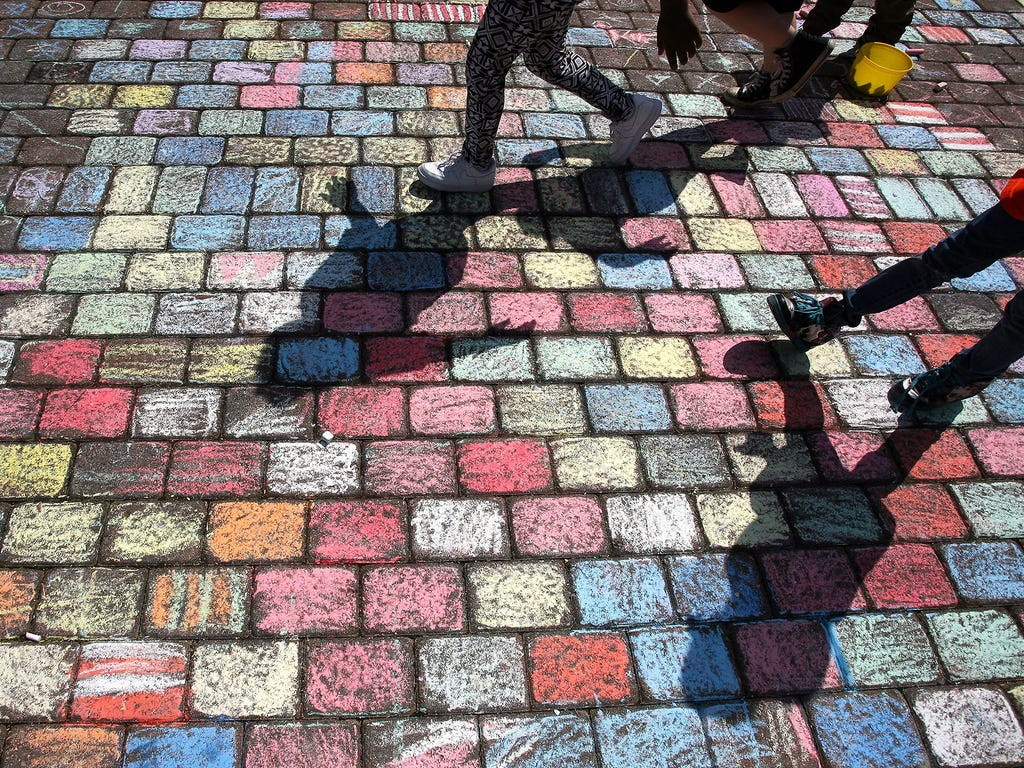 Elementary school students walk on paving stones covered with sidewalk chalk outside the school of nursing at Calhoun Community College on April 8 in Decatur, Ala.