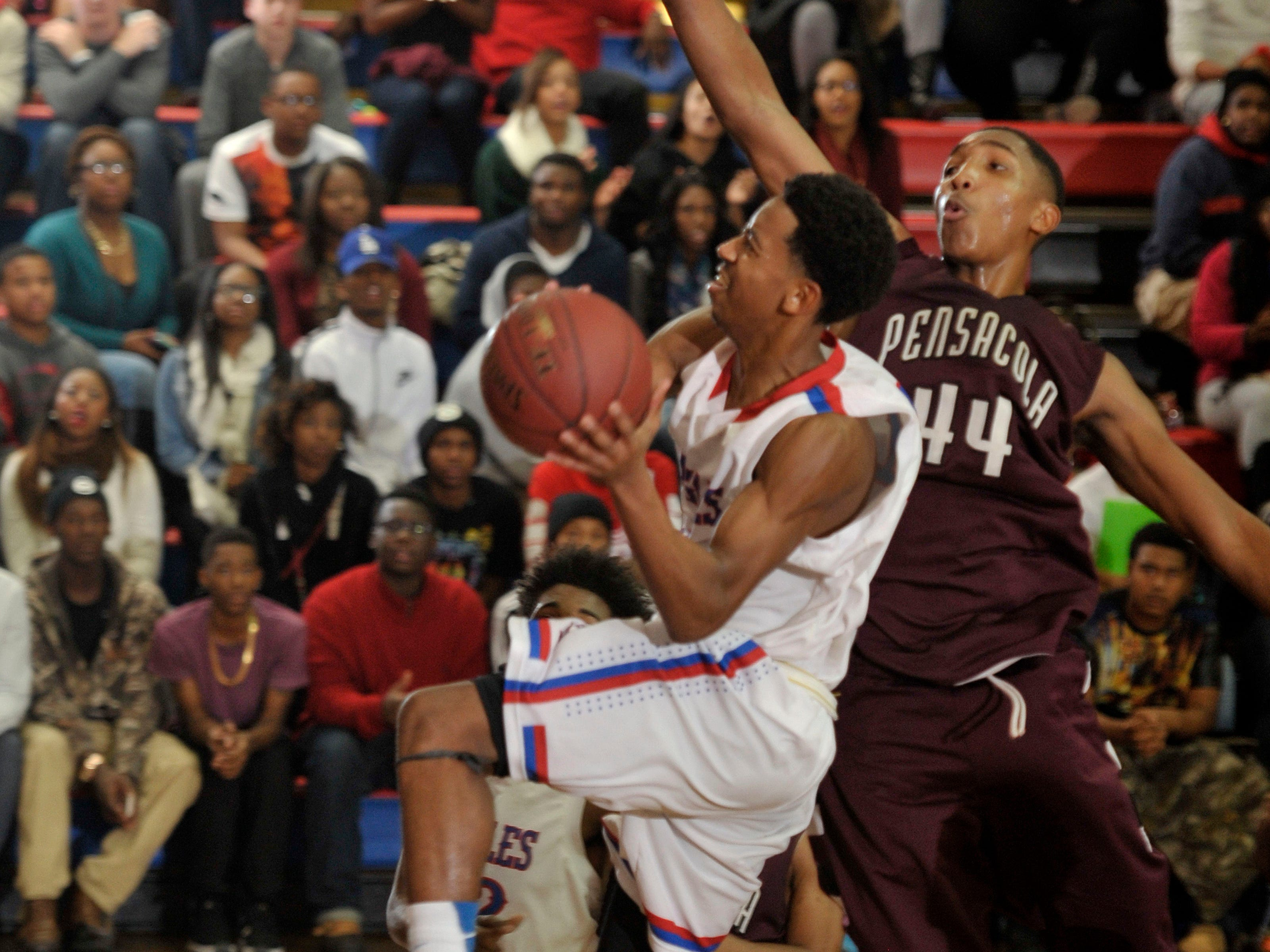 Devin Petters of the Pine Forest Eagles flies in attepting two points against defending Pensacola High Tigers No. 44, Devonchae Bryant, drawing a foul on Bryant in second-half action during their game Friday night at Pine Forest High.