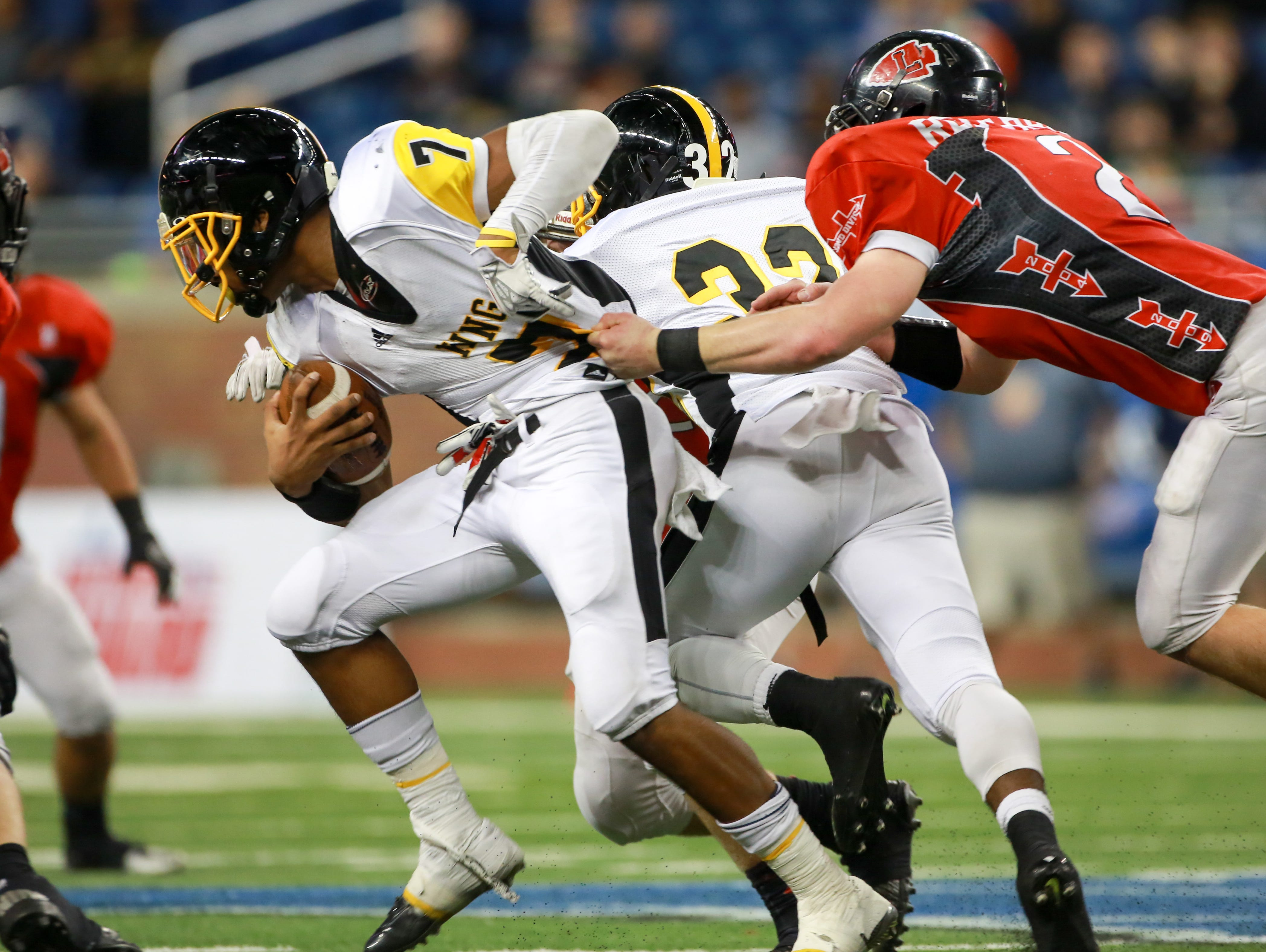 Detroit Martin Luther King QB Armani Posey tries to avoid being tackeld by Lowell LB Max Dean, during the second quarter of the Michigan High School Athletic Association football finals at Ford Field in Detroit on Friday, Nov. 27, 2015.