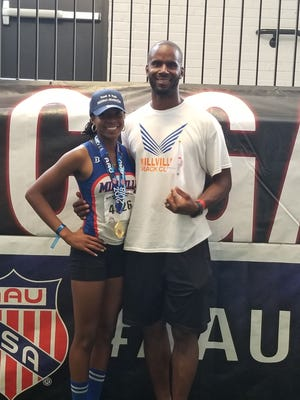 Bryanna Craig, left, stands with her father and coach, Raffael Craig, after winning the 14-year-old AAU Junior Olympics Pentathlon in July.
