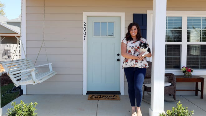 Erin Tapocik poses for a photo with her dog Pebbles on the front porch of her new home in Village Green. She was one of the first people to buy a house in the neighborhood, a mixed-use community on Hadley Avenue that will feature 46 single-family homes, five apartments, a half-acre park and about 5,000 square feet of commercial space.