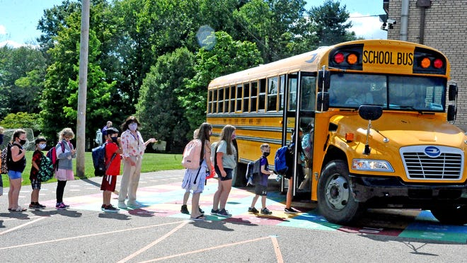 A row of masked Wooster Township Elementary School students load into the bus Wednesday after their first day of class.
