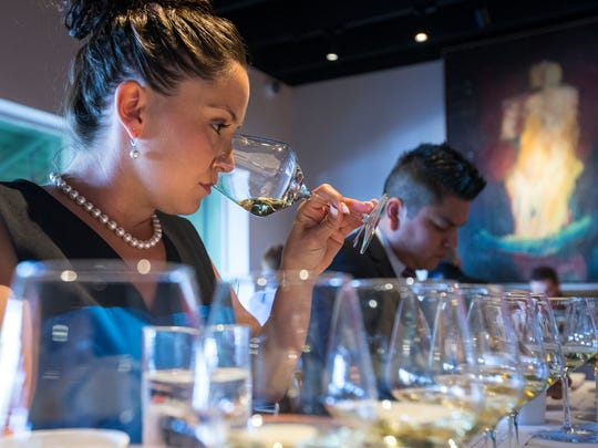 Noelle Waite, of Southern Wine & Spirits takes in the aroma of one of the white wines at The Arizona Republic Wine Competition at Tarbell's in Phoenix, on Monday, October 27, 2014. Twenty judges each graded 30 wines in the preliminary round, with around 140 Arizona wines competing for top honors.