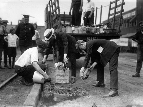 Rochester police property clerk Joseph Sheridan (right) led the pouring as illegal booze was dumped into a gutter during a Prohibition raid on a speakeasy in northeast Rochester. No date on photo.