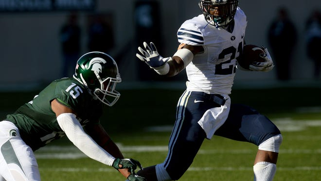 Michigan State University sophomore cornerback Tyson Smith (15) tries to tackle BYU senior running back Jamaal Williams (21) in the first half of MSU's game against BYU Saturday, October 8, 2016 in East Lansing.