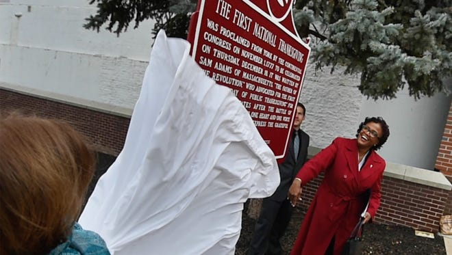 York County Commissioner Susan Byrnes, left, and York Mayor C. Kim Bracey unveil the repainted First National Thanksgiving sign in front of the York County Administrative Center on Tuesday.