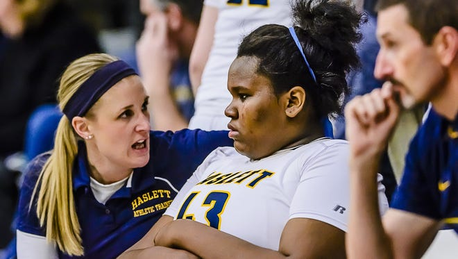 Imania Baker, center, of Haslett sheds a tear as a Haslett athletic trainer discusses her head injury with her at halftime of the DeWitt/Haslett game Friday February 17, 2017 in Haslett. Baker suffered a head injury in the 1st quarter and after a brief reappearance in the 2nd quarter, left the game not to return.